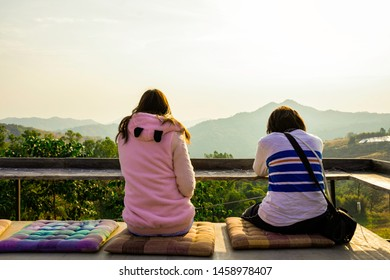 Asian girl relax with landscape nature mountain in the morning, Sit on balcany looking beautiful sunrise on the peak of mountain, Asian women wear jacket in winter with green nature view