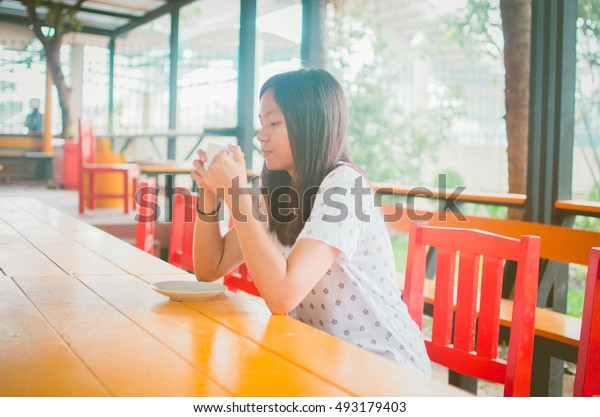 asian girl relaxing in coffee shop.thai woman.focus in front of her face.
