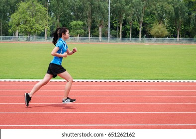 Asian girl is running on track.