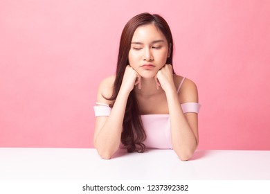Asian girl with sad emotion on pink background