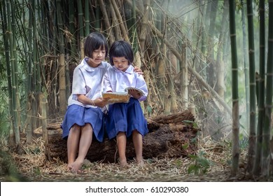 Asian girl in school uniform teaching a sister to read a book.
