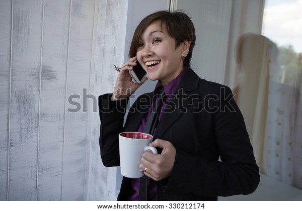 Asian girl in shirt talking on phone and smiling on a white background
