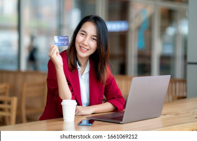 Asian girl shoping online by credit card in coffee shop.
