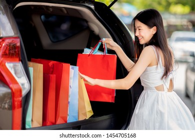 Asian girl shopping with mid year sales  promotion in department store and go to car park for keep her bag in the car