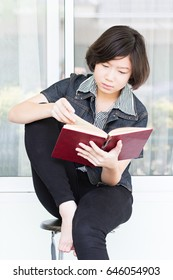Asian girl with short hair reading a book sitting on a chair