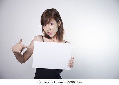 Asian girl show the white blank board. Young short hair Asian girl on white background.