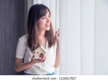 Asian girl showing and holding model house or rent new home or dreams about new home, buying new house concept