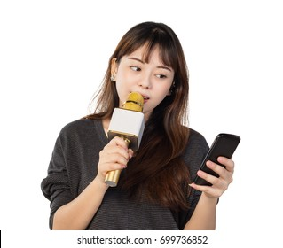 Asian girl singing using a wireless microphone while holding a phone