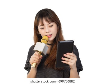 Asian girl singing using a wireless microphone while holding computer tablet