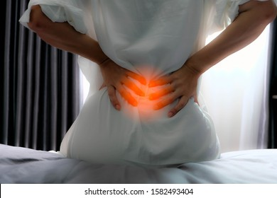 Asian girl sitdown at the bed and hold hand at low backache likes pain this area, may be happen from office syndrome or play sport. She's want to first aid or go to the hospital and meet the doctor