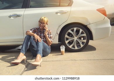Asian girl sitting beside her car and talk on the phone on the outdoors.Happy mood.Focus on hand