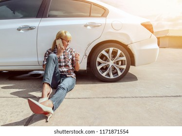 Asian girl sitting beside her car and talk on the phone on the outdoors.Happy mood.Focus on face