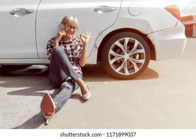 Asian girl sitting beside her car and talk on the phone on the outdoors. Happy mood. Focus on Face