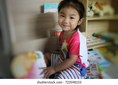 Asian girl sitting in living room reading book,Smiling little girl