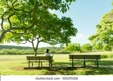an asian girl sitting on bench under the tree