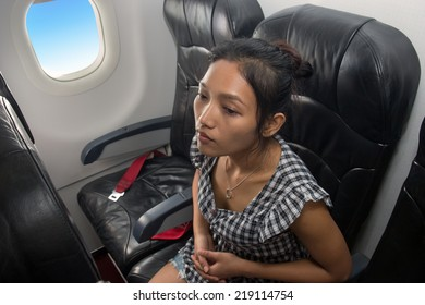 Asian girl sitting on the plane. A passenger in a flying aircraft. The traveler sits in Airplanes. Woman in summer dress sitting in an airplane flying in the blue sky. Asian traveler on the plane.