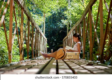 Asian girl sitting and reading a book on the bridge in forest