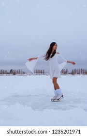 Asian girl skating in white dress outdoors at winter