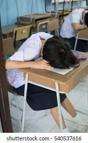 Asian girl sleep on the table in classroom