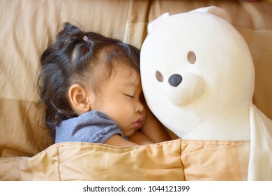 an asian girl sleeping on a pillow and put the blanket on and huging with her white bunny doll , kid healthy concept