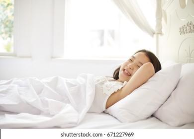 Asian girl sleeping on white bed.