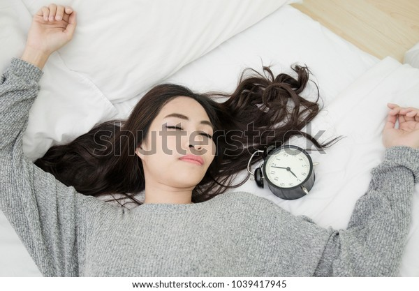 Asian girl sleeps a good dream in bed in a white bedroom.Asian girl wearing gray shirt Sleeping on a white bed And a black alarm clock next to it.