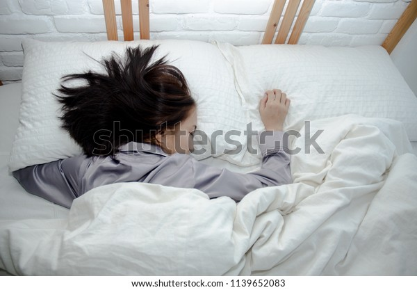 Asian girl sleeps in gray pajamas and shorts. On the bed in the white bedroom. The dark spots on the face of a young girl caused by sunlight.Cotton and sunny.