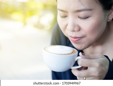 Asian girl smelling and enjoying cup of hot coffee at the outside of cafe. with sunlight effect.