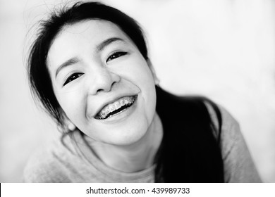 asian girl smile to camera,thai girl style has a smile to camera,land of smile, black and white high contrast picture style ,on white background, selective focus a eye