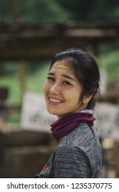 Asian girl smile with traditional thanaka makeup on her face