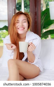 Asian girl smiles happily while sitting in white bed. In her hand holds a cup of coffee.