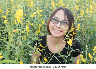 Asian girl smiling In the field of yellow flowers.