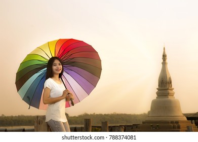 Asian girl smiling on standing and hold umbrella with sunset, in front of wooden bridge way to the Pagoda of Thailand, Ubon ratchathani - Pak nam temple (bung sa pang)
