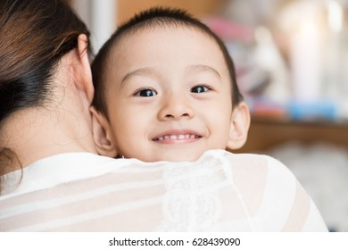 asian girl smiling and resting on her mother's shoulder.