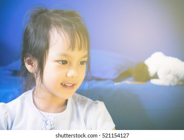 Asian girl smiling sitting on a blue sofa