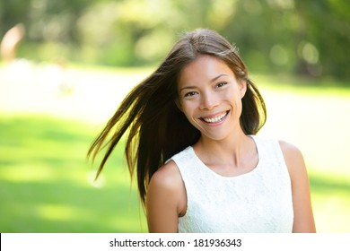 Asian girl spring portrait in park. Smiling happy mixed race Asian Caucasian woman in 20s looking at camera.