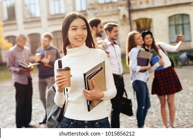 An asian girl is standing in the courtyard of the university with books in her hands. Near her friends. They are students.