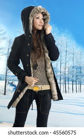 A asian girl stands in snow for fashion pose