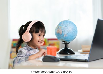 Asian girl student is happy learning online class at home and smiling with friend and teacher in video, concept of online education and new normal of studying trend in the outbreak of corona virus.