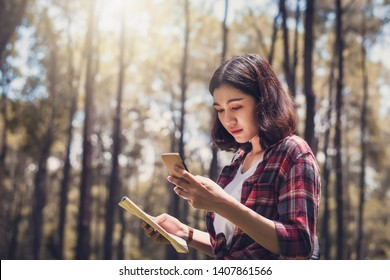 Asian girl student holding a map in hand and checking for GPS signal from smartphone in forest at the camp.
