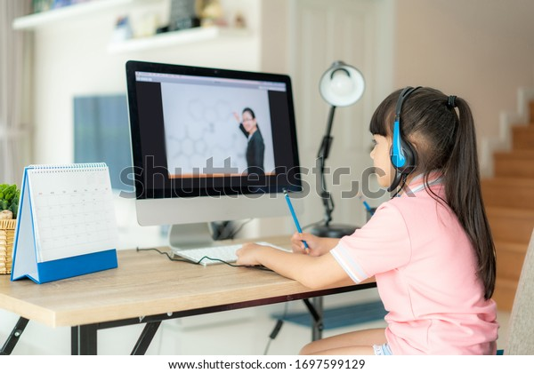 Asian girl student video conference e-learning with teacher on computer in living room at home. Homeschooling and distance learning ,online ,education and internet protect from COVID-19 viruses.