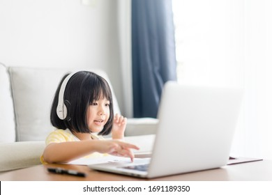 Asian girl student wear wireless headphone study online with video call teacher, Happy young girl learning earth ecology listen lecture watch write notes look at laptop at home.Covid-19 coronavirus.