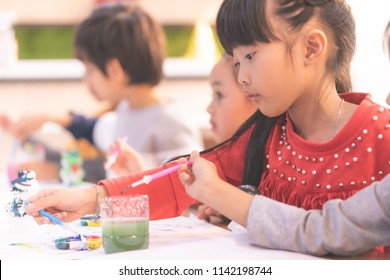 Asian girl students is drawing water painting in kindergarten art classroom for Small children creativity educational concept.