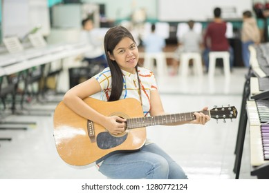 Asian girl studyguitar in the music classroom