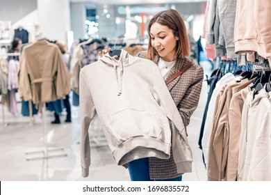 Asian girl stylist chooses clothes for her casual look in a modern mass market store