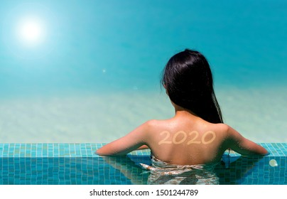 Asian girl with sunscreen in form of 2020 number on her back sunbathing in swimming pool. Sunburn tan lines of 2020 word. Back of woman with red painful skin after sunbathing. Sun protection factor.