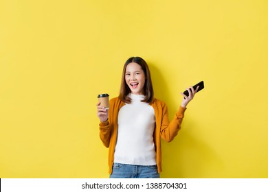 Asian girl is surprised she is excited. In mobile phone with coffee yellow background, studio