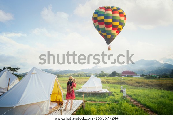 Asian girl take a hot air balloon photo by camera in homestay in rice farm in Pua, Nan province, Thailand. This image can use for home stay, hotel, resort, holiday, travel, park and outdoor concept