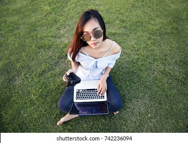 asian girl take look at digital camera in park with sunglasses