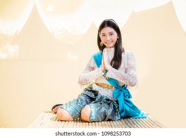 """asian girl in thai vintage costume siting and greeting action on brown silhouette thai hose background. Greeting with hand in Thai tradition call """"Sawasdee""""."""